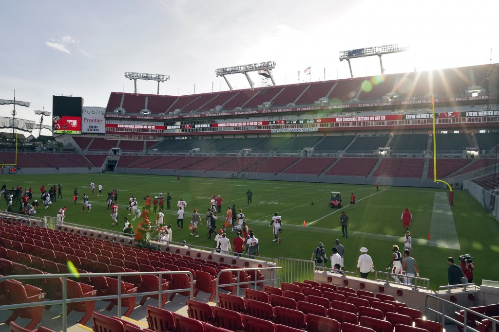 The sun rises over Raymond James Stadium as the Tampa Bay Buccaneers take the field for an NFL football training camp practice Friday, Aug. 28, 2020, ...