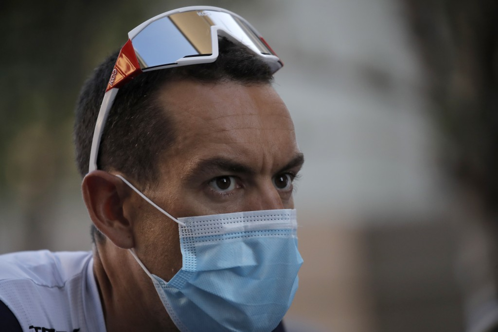 Australia's Richie Porte wears a face mask as he arrives for the 107th Tour de France cycling race team presentation, in Nice, southern France, Thursd...
