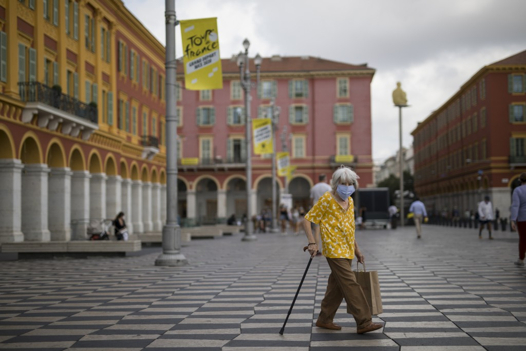 A woman wearing a mask to protect against the coronavirus walks through the Place Massena in Nice, southern France, Friday, Aug 28, 2020. The Tour de ...