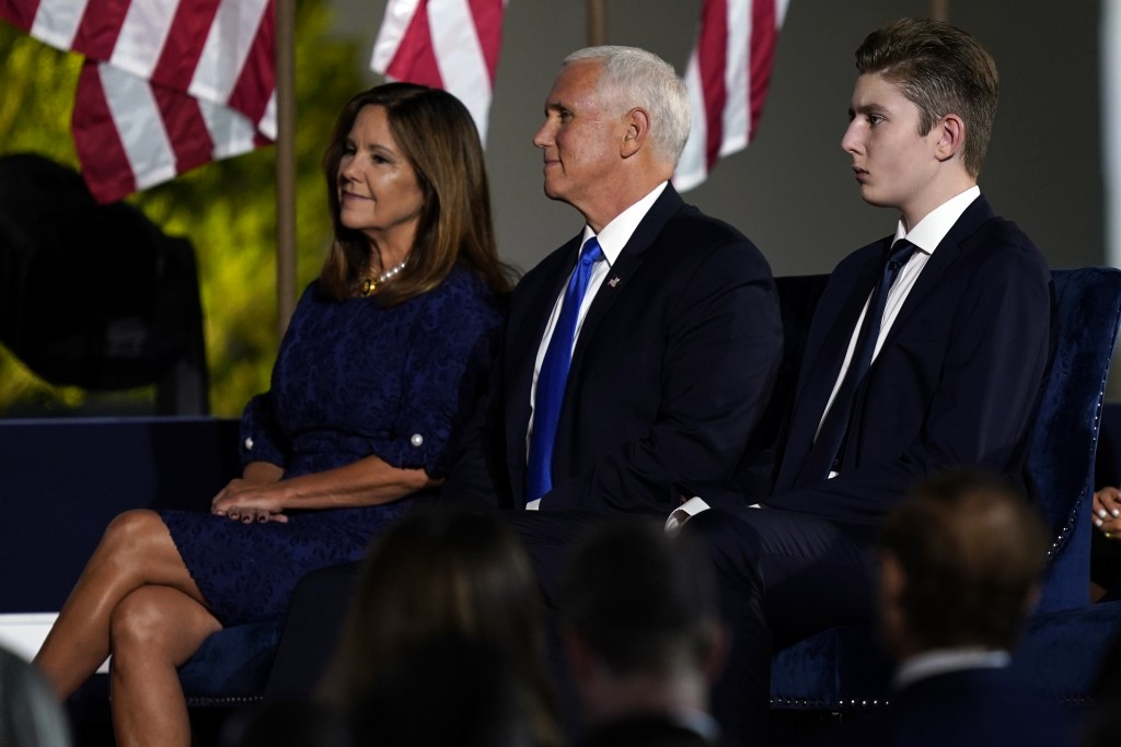 Barron Trump sits next to Vice President Mike Pence and Karen Pence as they wait for President Donald Trump to speak from the South Lawn of the White ...