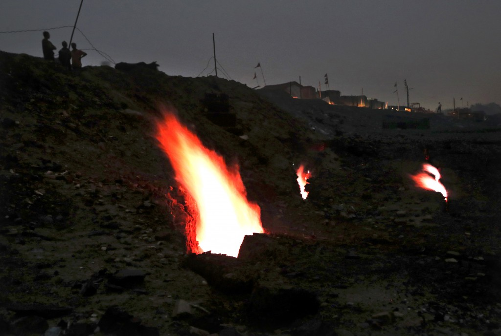 FILE- In this Oct. 23, 2019 file photo, flames rise from fissures in the ground above coal mines in the village of Liloripathra in Jharia, in the east...