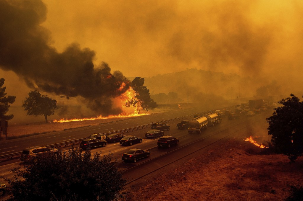 FILE - In this Wednesday, Aug. 19, 2020, file photo, flames from the LNU Lightning Complex fires jump Interstate 80 in Vacaville, Calif. The highway w...