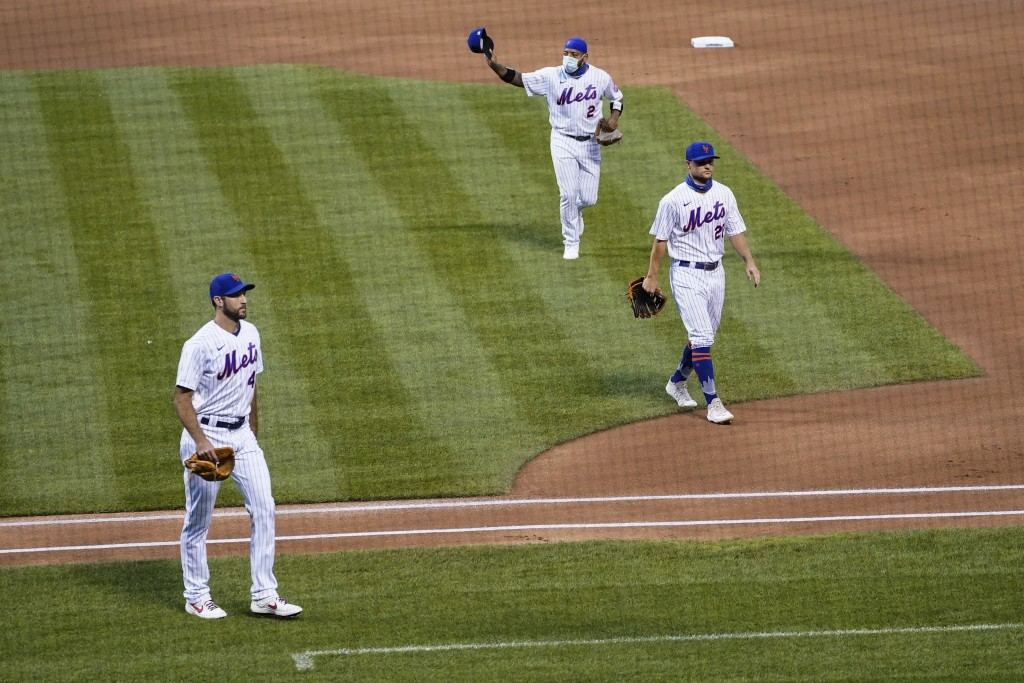 New York Mets left fielder Dominic Smith (2) tips his hat to the Miami Marlins as both teams walk off the field before a scheduled baseball game Thurs...
