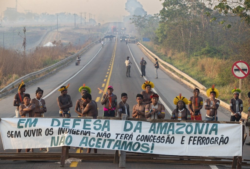 "Kayapo Indigenous protesters block highway BR-163 with a banner that reads in Portuguese ""Defending the Amazon. Without listening to Indigenous people..."