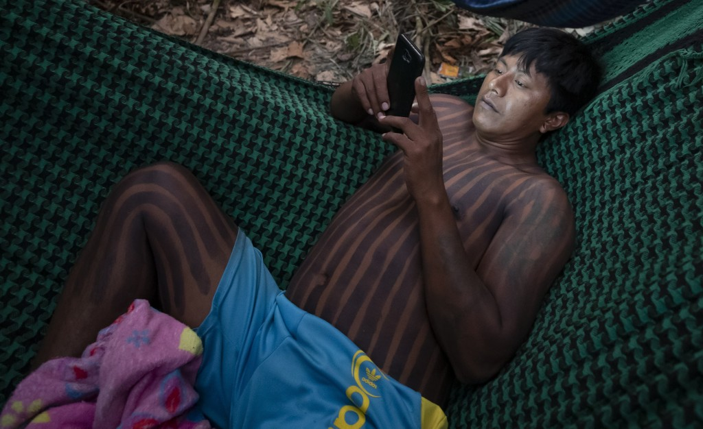 A Kayapo Indigenous man checks his cellphone while resting in a hammock after the temporary suspension of a protest where his group blocked Highway BR...