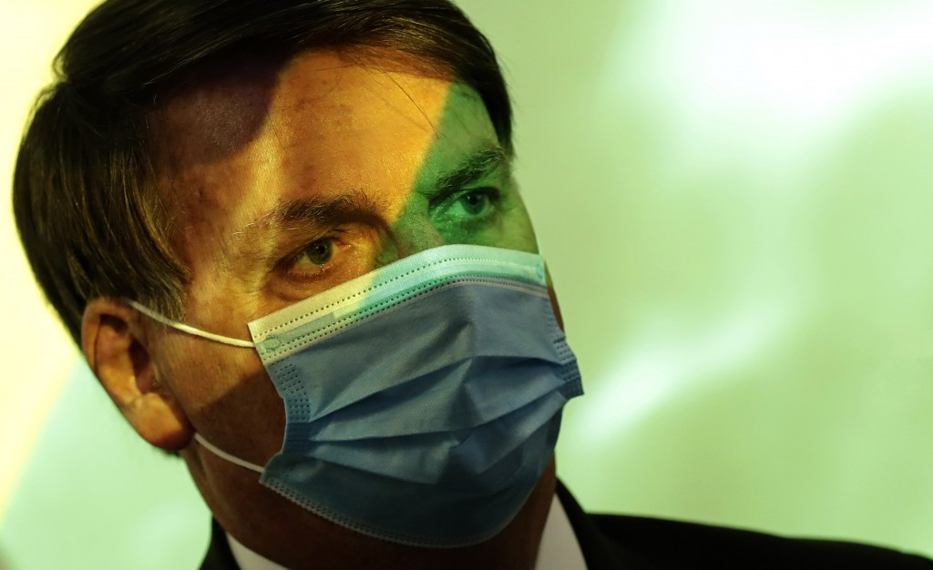 Brazil's President Jair Bolsonaro wears a mask amid the COVID-19 pandemic at the start of a ceremony where his nation's flag is projected over him in ...