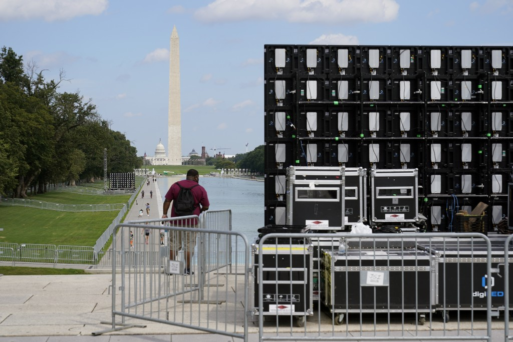 With the Washington Monument in the background, people walk by equipment being set up near the reflection pool on Thursday Aug. 27, 2020, in Washingto...