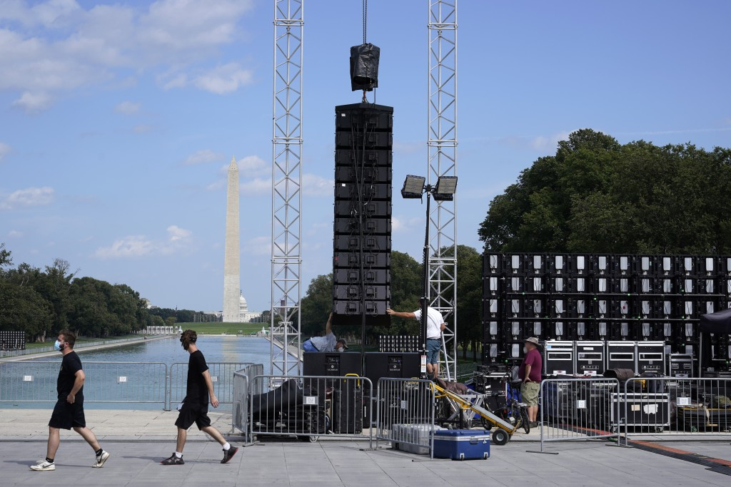 With the Washington Monument in the background, people set up equipment near the reflection pool on Thursday Aug. 27, 2020, in Washington, prior to th...