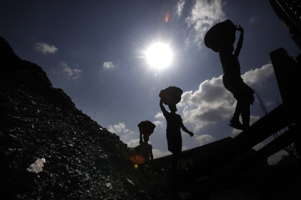 FILE- In this Oct. 20, 2010 file photo, Indian laborers carry coal to load on a truck in Gauhati, India. India should commit to carbon neutrality by e...