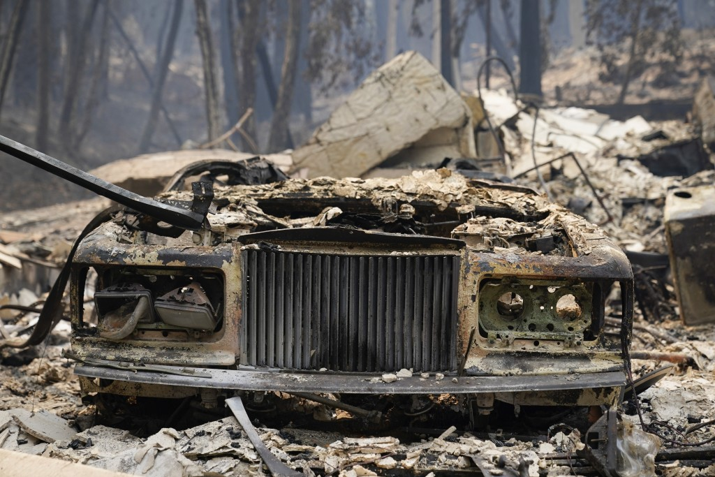 FILE - In this Sunday, Aug. 23, 2020, file photo, a charred vehicle is parked in front of a home after the CZU Lightning Complex Fire went through in ...