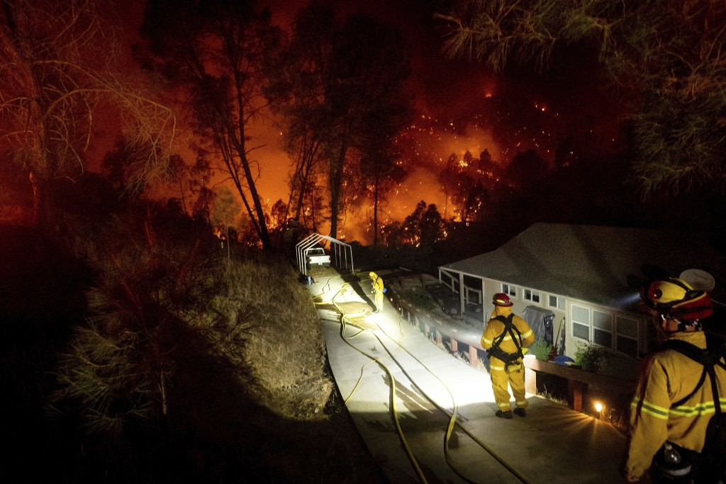 FILE - In this Friday, Aug. 21, 2020, file photo, firefighters protect a home in the Berryessa Estates neighborhood of unincorporated Napa County, Cal...