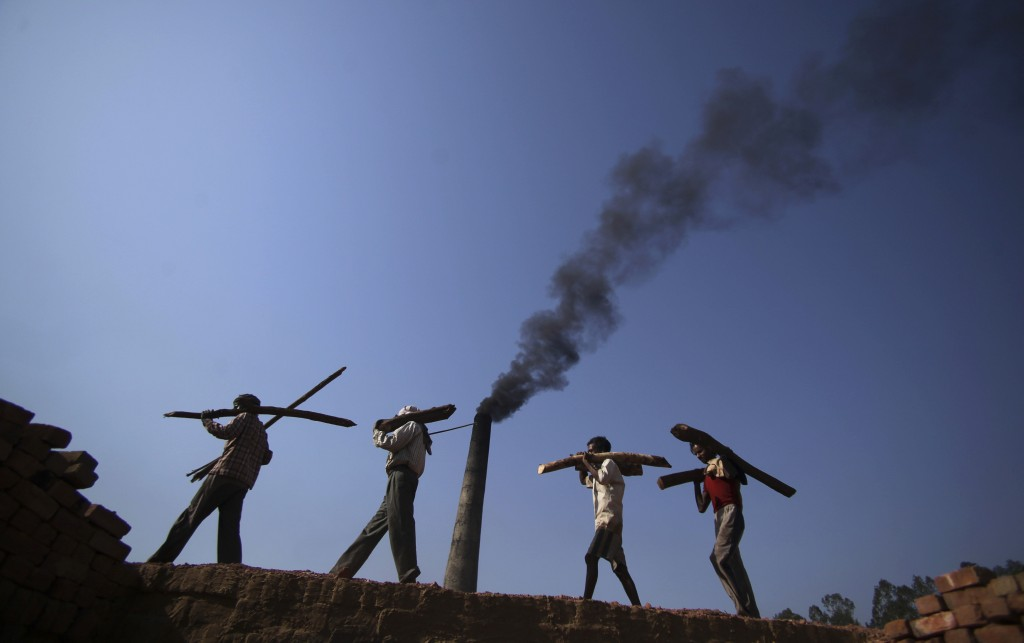 FILE- In this June 4, 2011 file photo, Indian laborers carry firewood, as smoke rises from a bricks factory on the outskirts of Jammu, India. India sh...