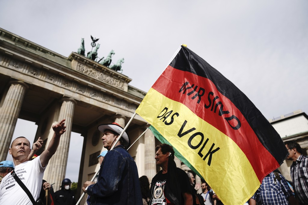 "A participant of a demonstration against the Corona measures holds a German flag with the writing ""We are the people"", the motto of the 1989 revolutio..."