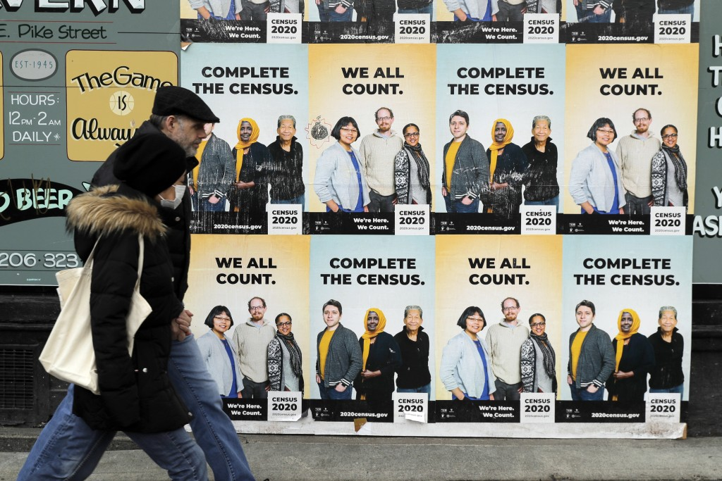 FILE - In this April 1, 2020, file photo, people walk past posters encouraging participation in the 2020 Census in Seattle's Capitol Hill neighborhood...