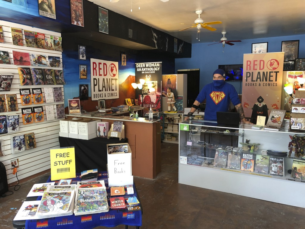 In this Aug. 19, 2020, photo, Aaron Cuffee poses at work at Red Planet Books & Comics in Albuquerque, N.M. Marvel Comics has assembled a gallery of Na...
