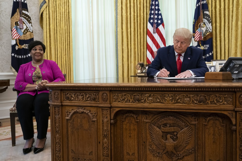 President Donald Trump signs a full pardon for Alice Johnson in the Oval Office of the White House, Friday, Aug. 28, 2020, in Washington. (AP Photo/Ev...