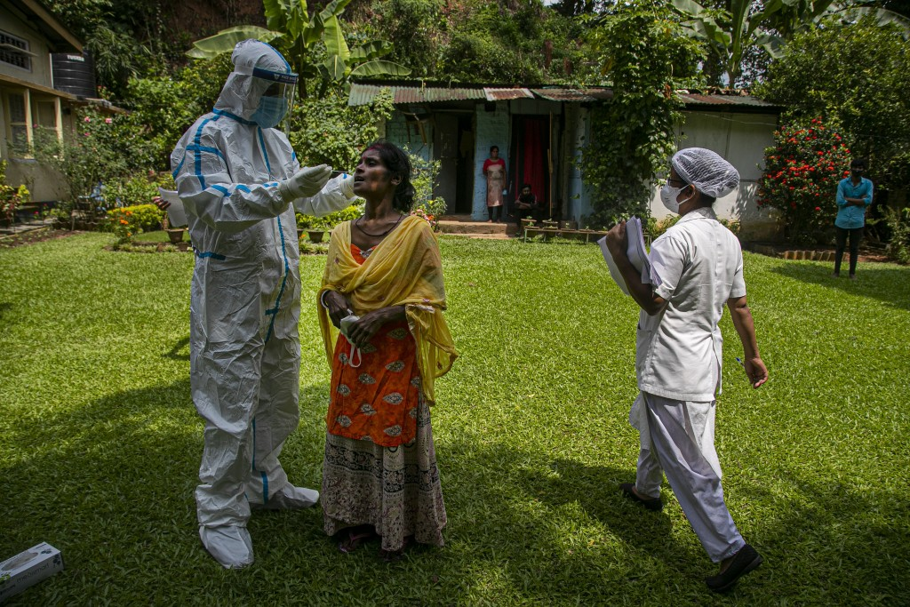 A health worker takes a nasal swab sample to test for COVID-19 during a door to door test drive in Gauhati, India, Saturday, Aug. 29, 2020. India has ...