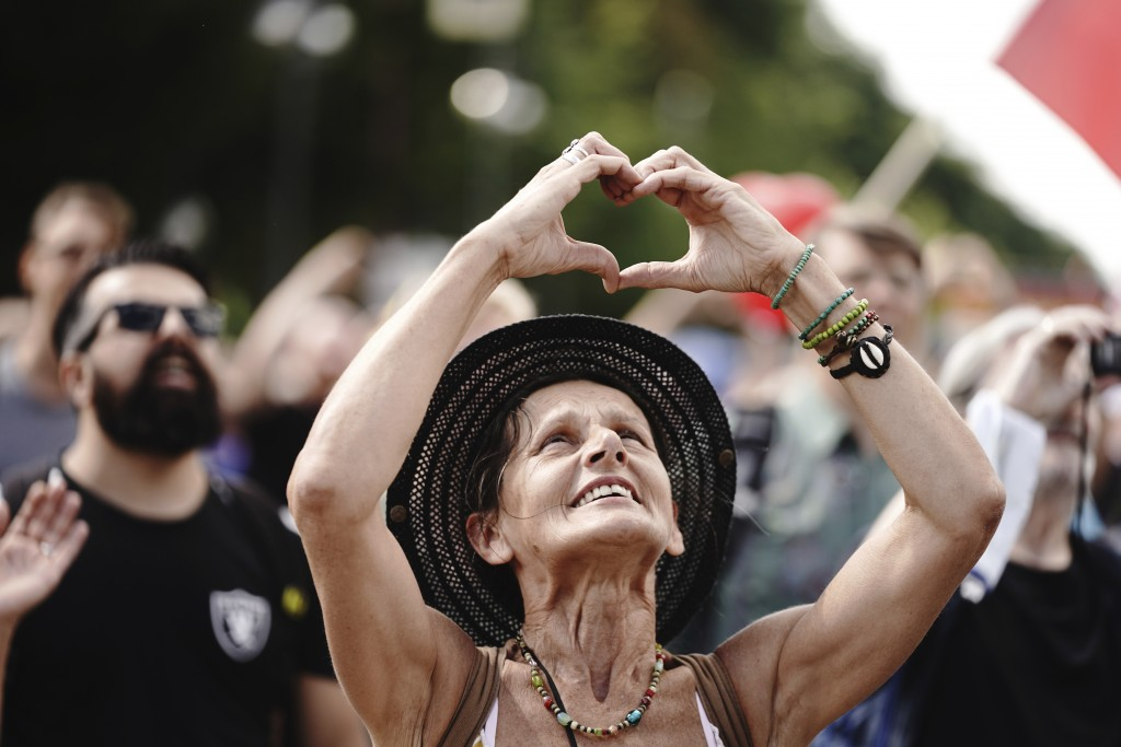 A participant forms a heart with her hands during a demonstration against the corona measures of the German Government in Berlin, Germany, Saturday, A...