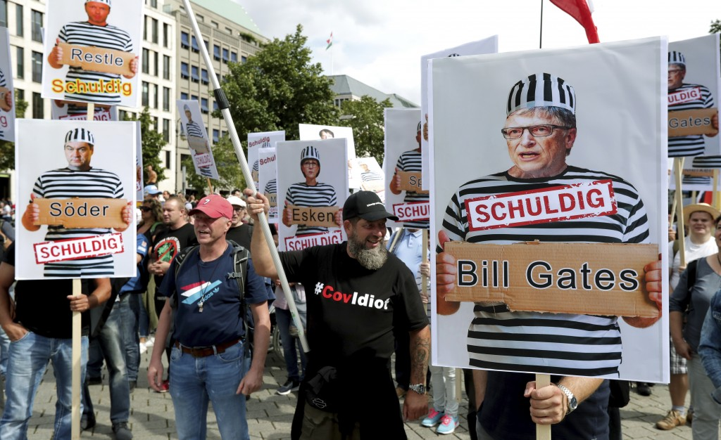 People attend a protest rally in Berlin, Germany, Saturday, Aug. 29, 2020 against new coronavirus restrictions in Germany, holding a sign with Bill Ga...