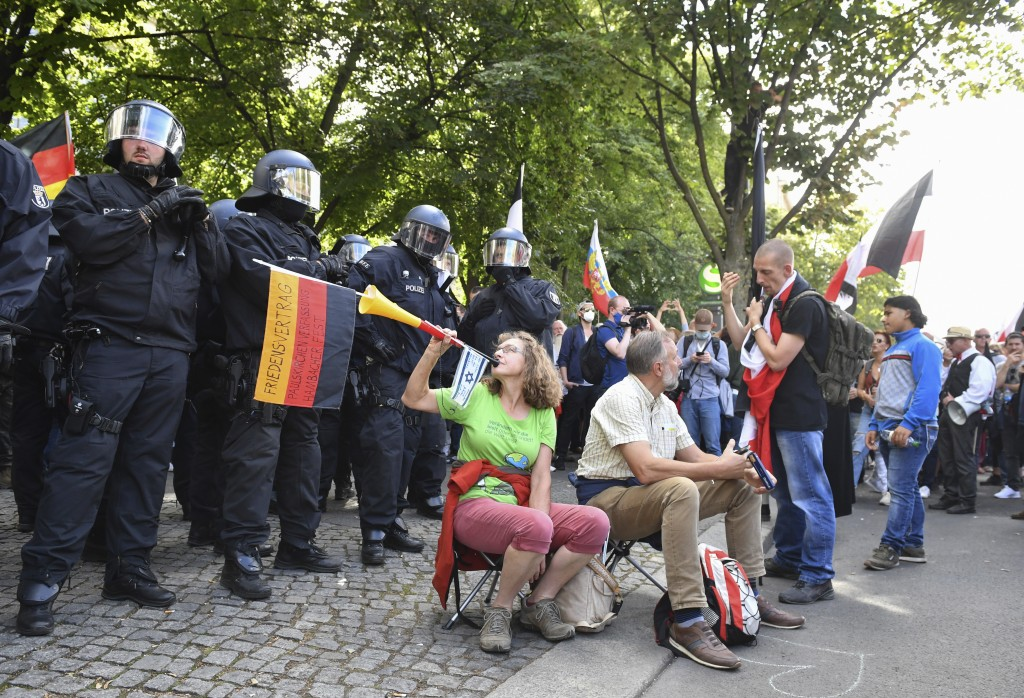 The participant in a demonstration against the Corona measures blows into a vuvuzela with a German and an Israeli flag in front of a police chain in B...