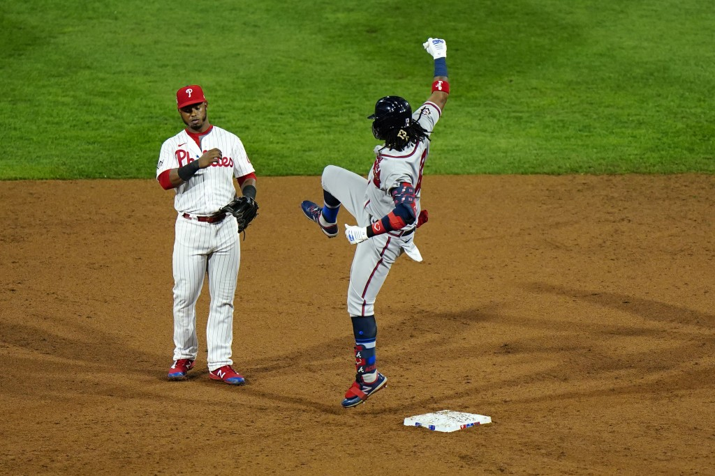 Atlanta Braves' Ronald Acuna Jr., right, playfully leaps at Philadelphia Phillies second baseman Jean Segura after hitting a double off pitcher Zack W...