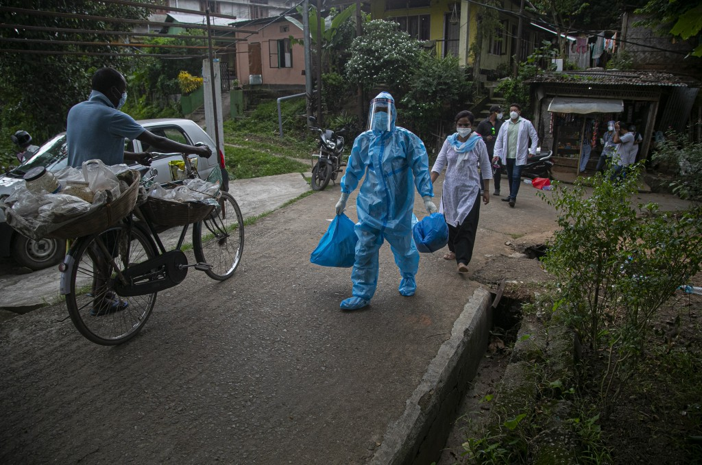 A health worker walks during a door-to-door drive to take nasal swab samples to test for COVID-19 in Gauhati, India, Saturday, Aug. 29, 2020. India ha...