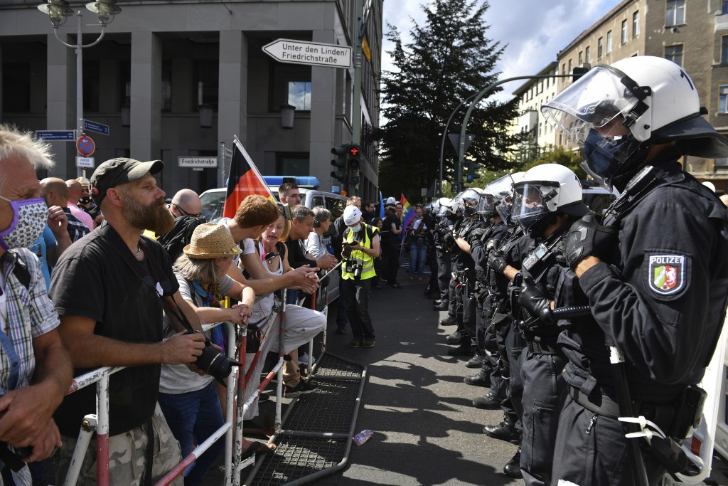 A police chain stands opposite the participants in a demonstration against the Corona measures at barrier bars in Berlin, Germany, Saturday, Aug. 29, ...