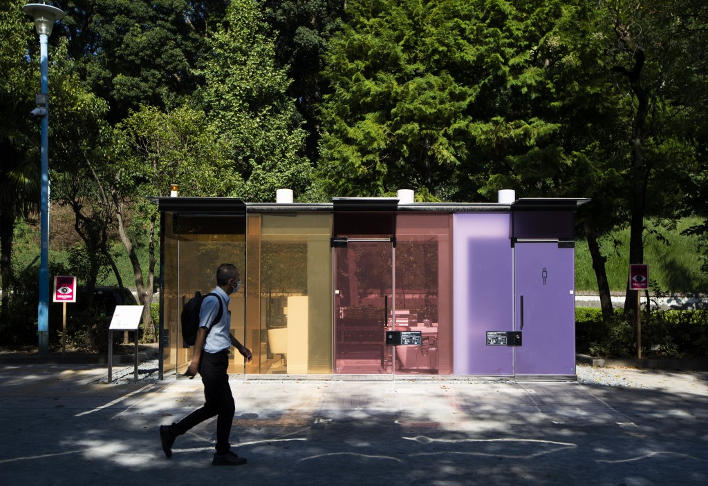 A man walks by the transparent glass toilets at Yoyogi Hukamachi Mini Park in Tokyo on Thursday, Aug. 20, 2020. The bathroom with the opaque (purple c...