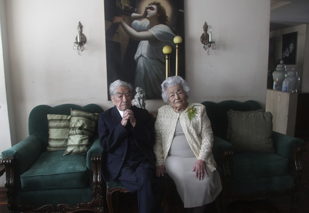 Married couple Julio Mora Tapia, 110, and Waldramina Quinteros, 104, both retired teachers, pose for a photo at their home in Quito, Ecuador, Friday, ...