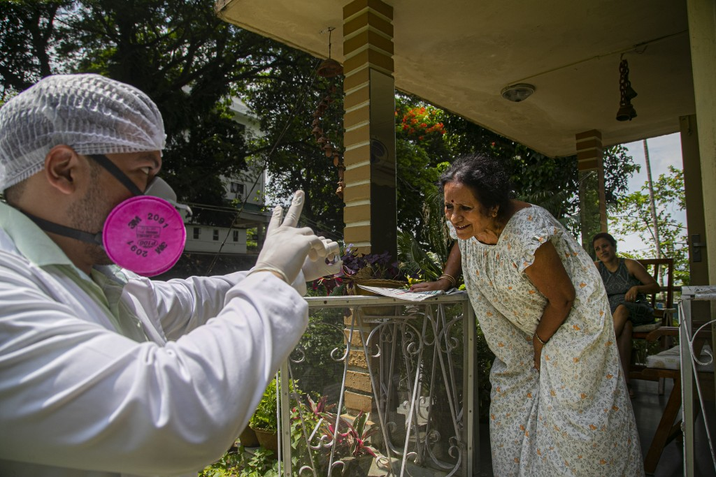 A health worker shows the result of a nasal swab test for COVID-19 during a door to door test drive in Gauhati, India, Saturday, Aug. 29, 2020. India ...