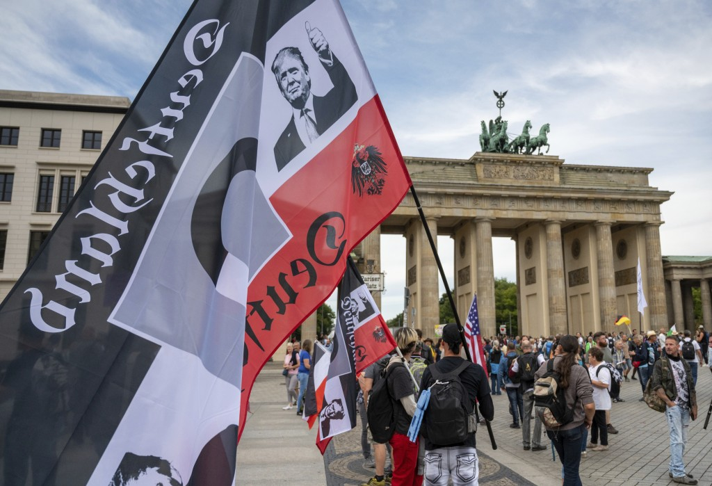 A protestor holds a flag of the German Reich with a picture of US President Donald Trump in front of the Brandenburg Gate before a demonstration again...