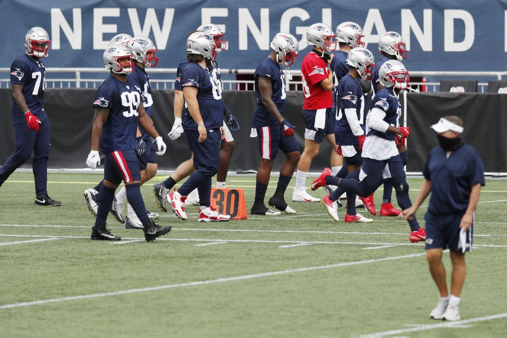 New England Patriots players take the field before an NFL football training camp scrimmage, Friday, Aug. 28, 2020, in Foxborough, Mass. Head coach Bil...