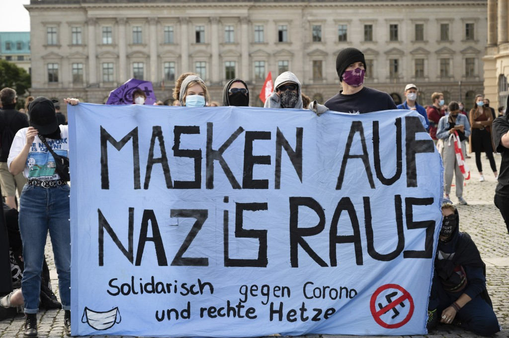 "Counter-demonstrators of a rally against the Corona measures gather and hold out a banner reading ""Masks on Nazis out"" in Berlin, Germany, Saturday, A..."