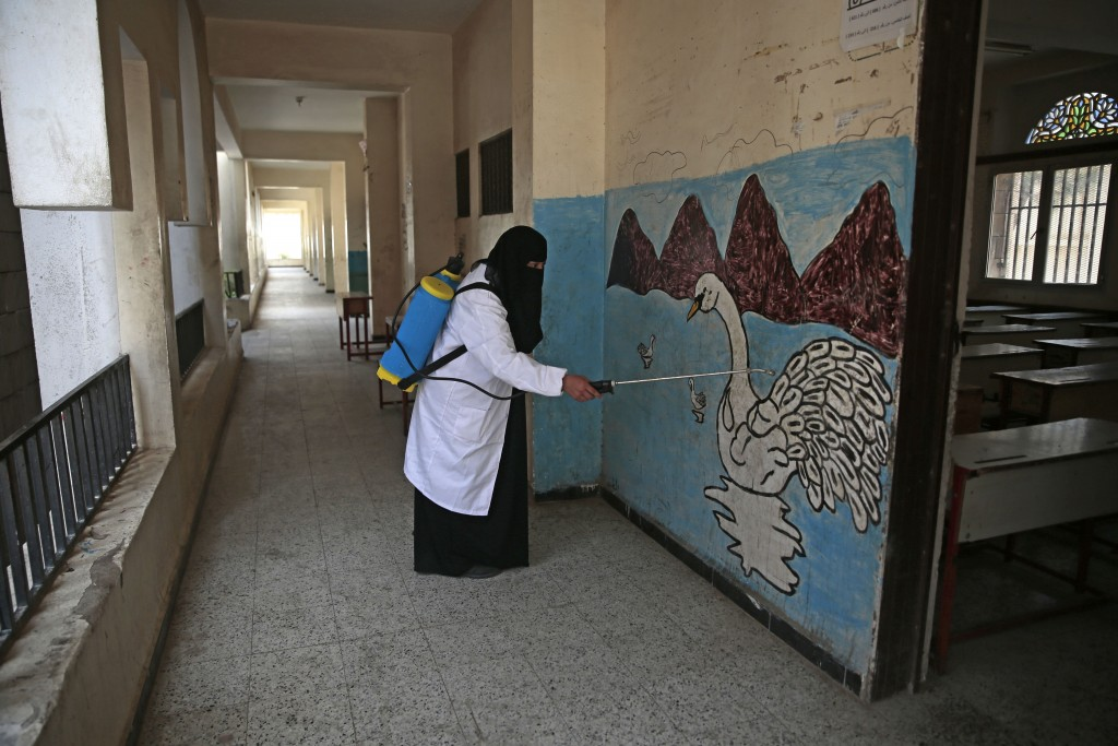 A worker disinfects a school as a preventive measure against the spread of the new coronavirus before students taking a final-term school exam at a pu...