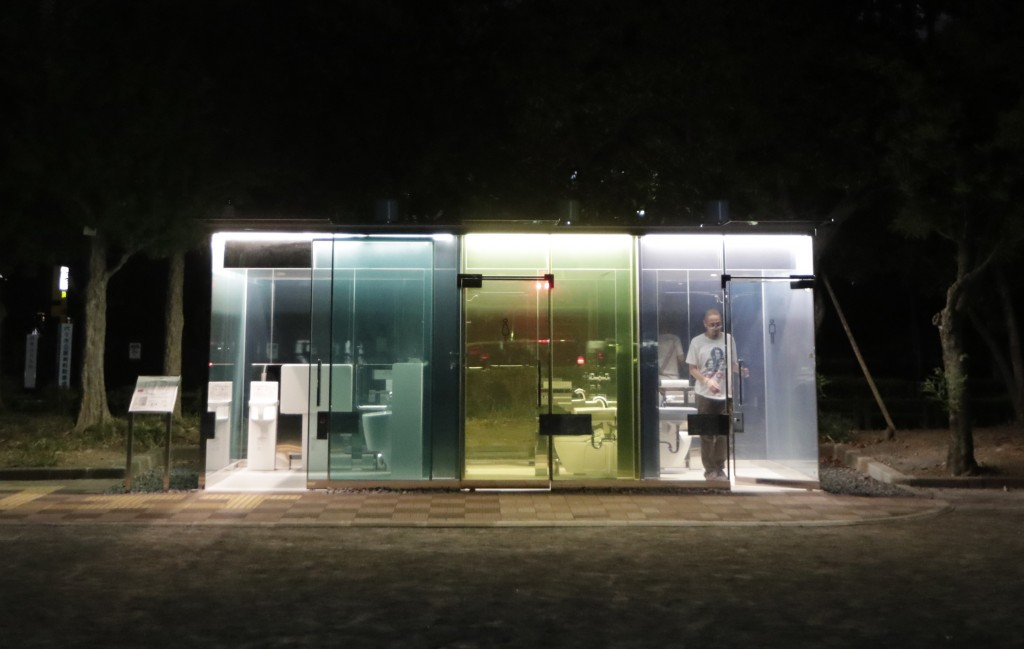 A man gets seen through the transparent toilet as he unlocked the door after use at Haru-no-Owaga Community Park in Tokyo on Thursday, Aug. 27, 2020. ...