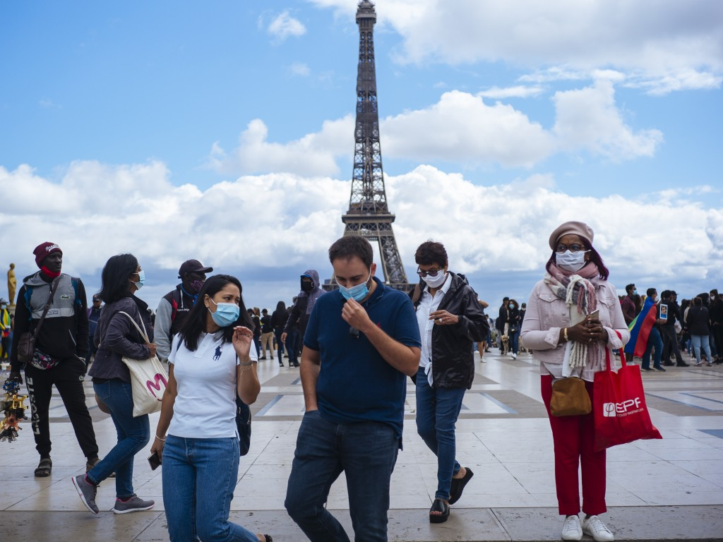 People wearing face masks stroll at Trocadero plaza near the Eiffel Tower, in Paris, Saturday, Aug. 29, 2020. France registered more than 7,000 new vi...