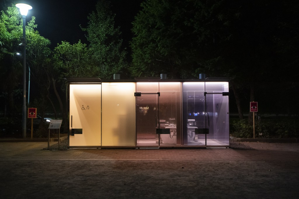 This photo shows the transparent glass toilets at Yoyogi Hukamachi Mini Park in Tokyo on Thursday, Aug. 20, 2020. The bathroom with the opaque (orange...