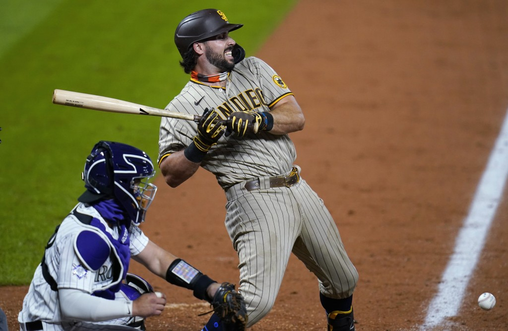 San Diego Padres' Austin Hedges grimaces after being hit by a pitch from Colorado Rockies reliever Yency Almonte, next to catcher Tony Wolters during ...
