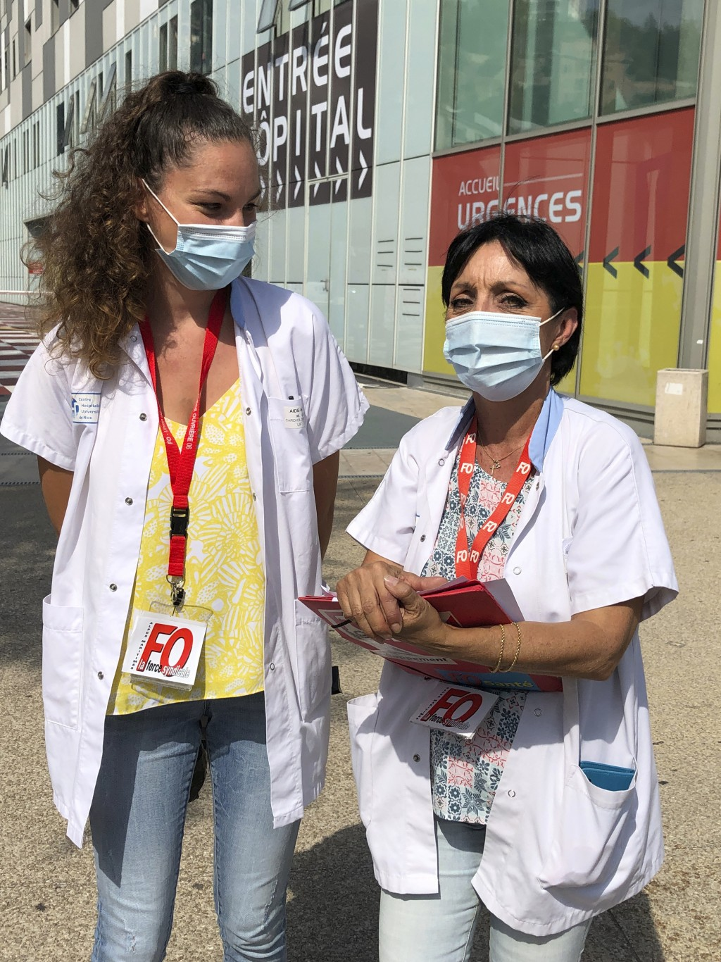 Caregiver Maude Leneveu, left, and union representative Corinne Bryand, pose outside the Pasteur hospital where they work in Nice, southern France, an...