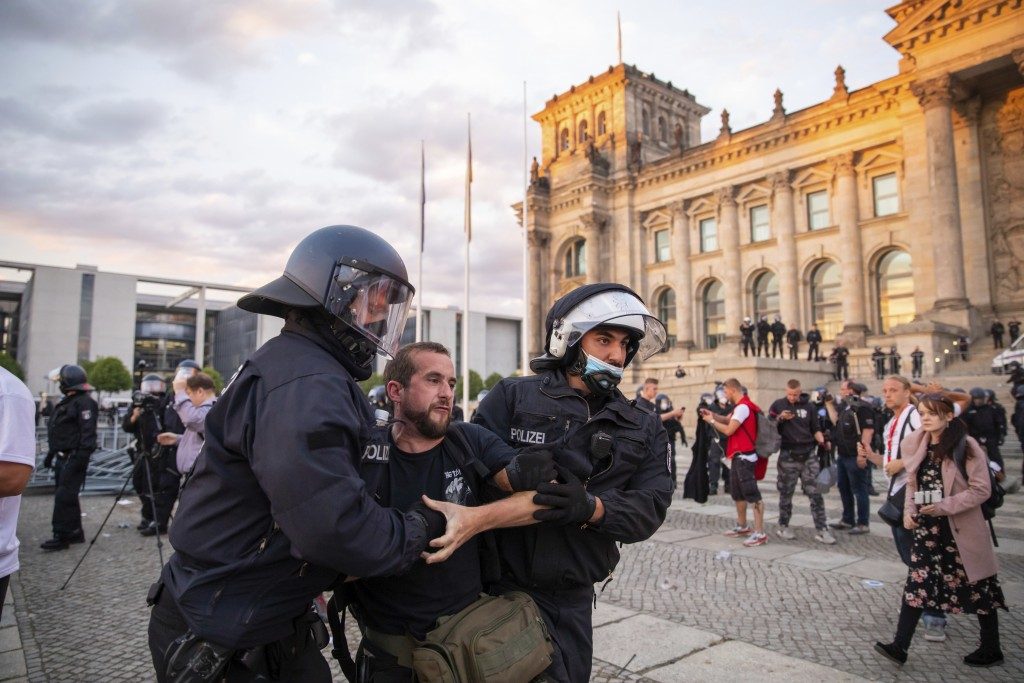 Police officers push away a crowd of demonstrators from the square 'Platz der Republik' in front of the Reichstag building during a demonstration agai...