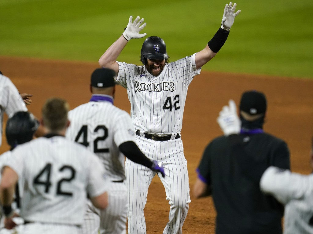 Colorado Rockies pinch-hitter Daniel Murphy, top,, celebrates after his walkoff RBI-single off San Diego Padres relief pitcher Craig Stammen in the ni...