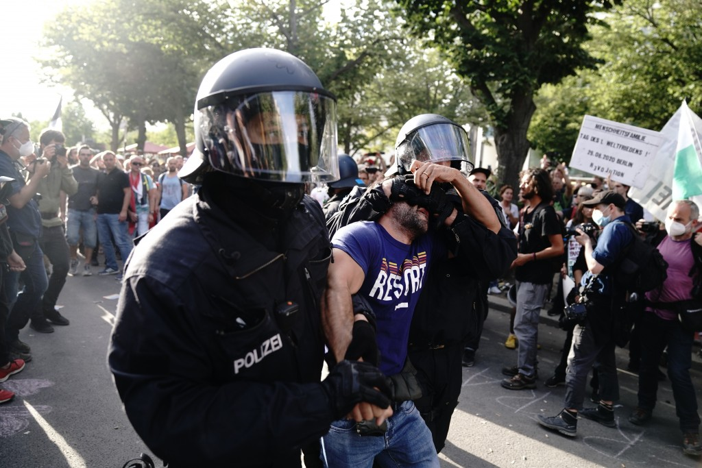 Police take a man away at the boulevard Unter den Linden during a protest against Corona measures in Berlin, Germany, Saturday, Aug. 29, 2020. (Kay Ni...