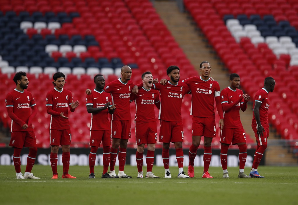 Liverpool players stand on the pitch during the penalty shootout during the English FA Community Shield soccer match between Arsenal and Liverpool at ...