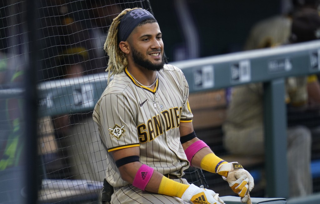 San Diego Padres' Fernando Tatis Jr. smiles as he waits to bat in the on-deck circle in the first inning of a baseball game against the Colorado Rocki...
