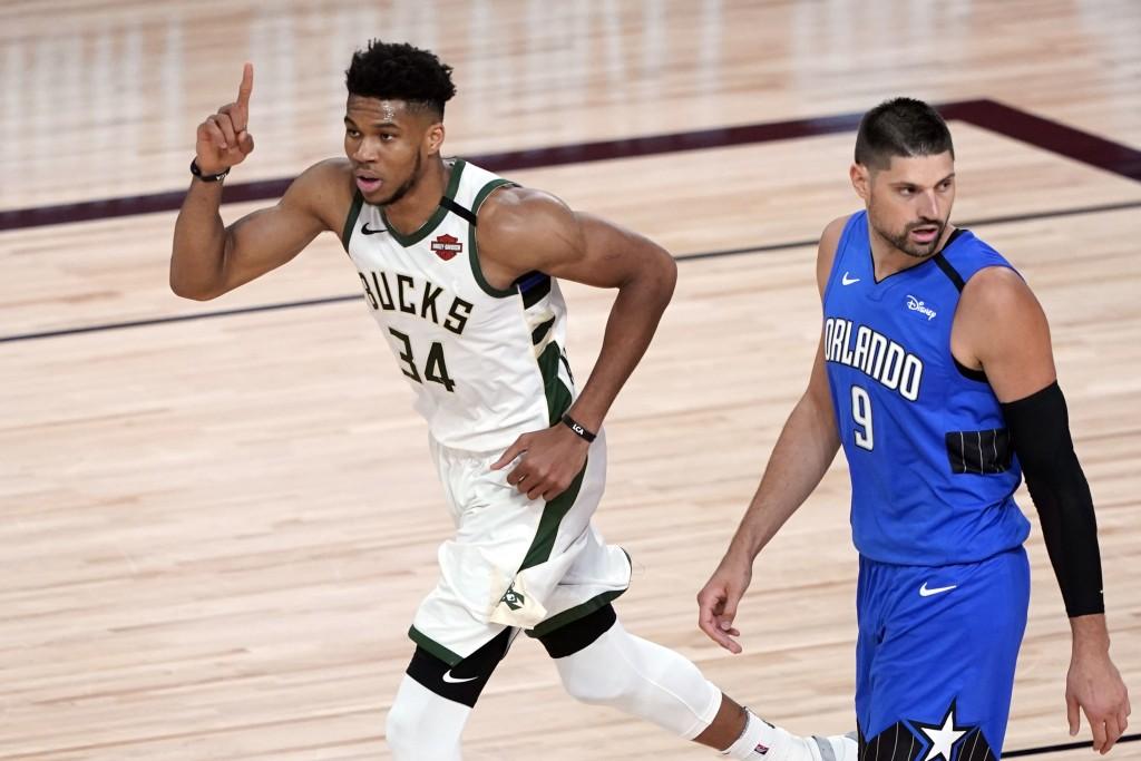 Milwaukee Bucks' Giannis Antetokounmpo (34) celebrates after a dunk as Orlando Magic's Nikola Vucevic (9) looks back during the first half of an NBA b...