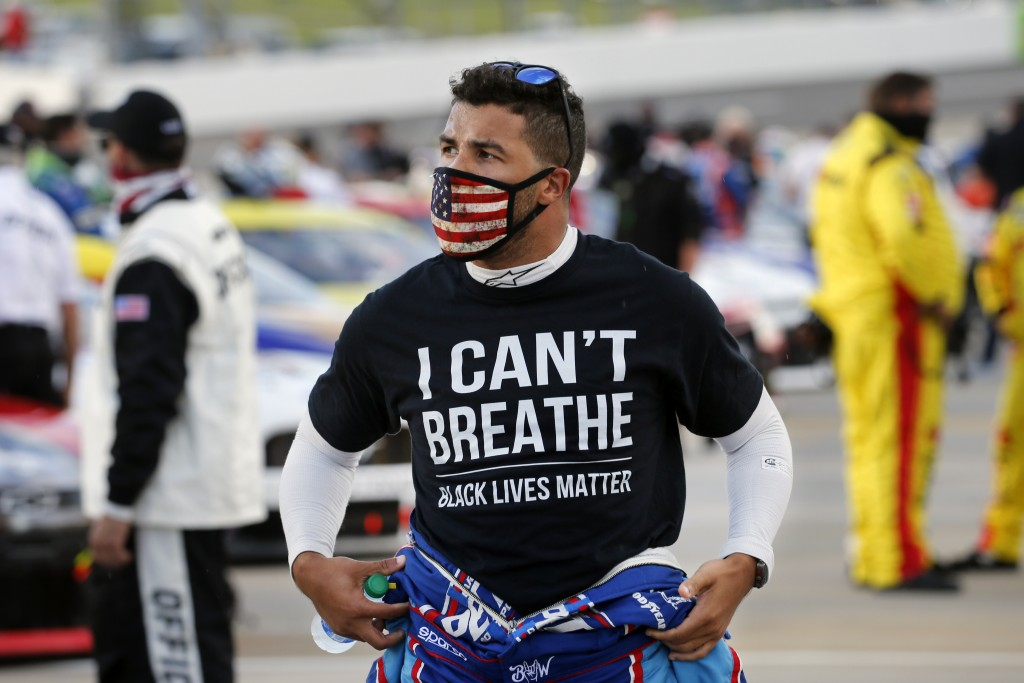FILE - Driver Bubba Wallace wears a Black Lives Matter shirt as he prepares for a NASCAR Cup Series auto race Wednesday, June 10, 2020, in Martinsvill...
