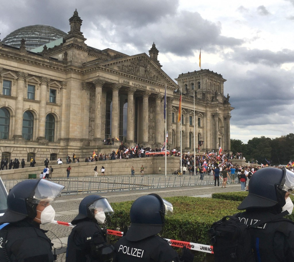 Police officers looks to protestors standing on the steps in front of the Reichstag building during a demonstration against the Corona measures in Ber...