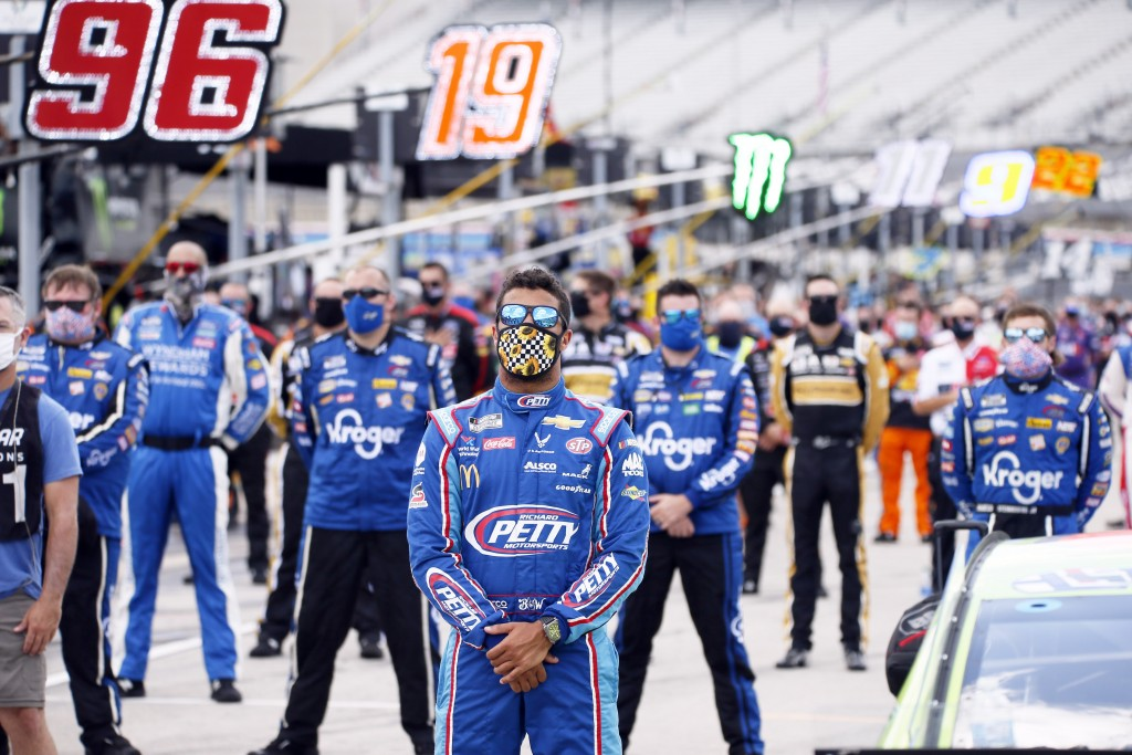 """FILE - Bubba Wallace, center, stands on pit road during the playing of """"America the Beautiful"""" prior to a NASCAR Cup Series auto race at Texas Motor S..."""