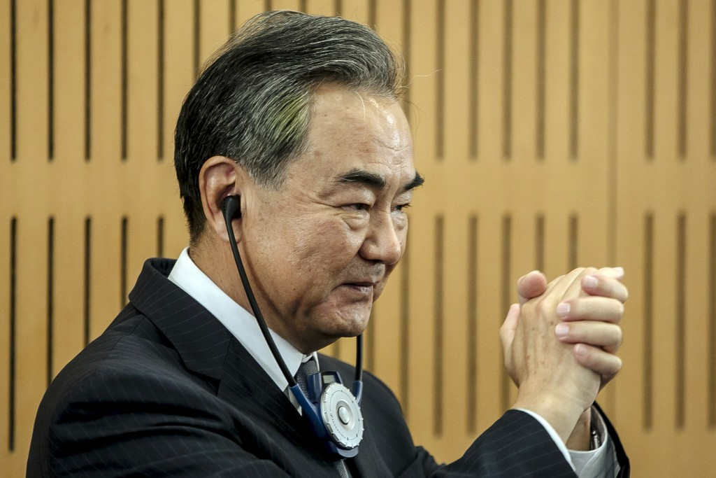 Chinese Foreign Minister Wang Yi greets the audience prior a press conference at the Institute for International Relations in Paris, Sunday, Aug. 30, ...