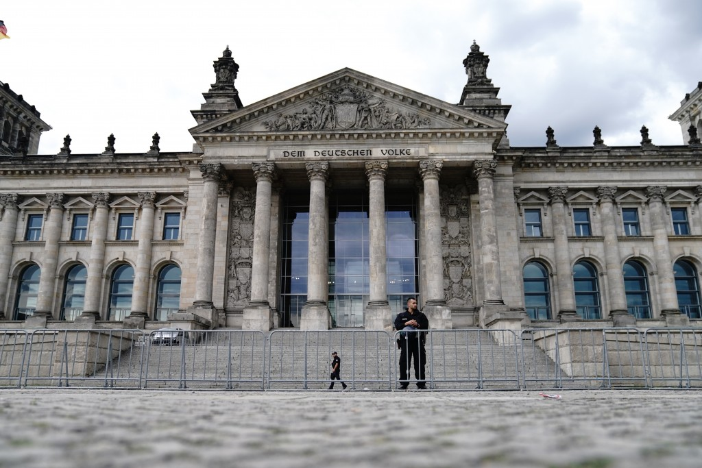 Police officers secure the Reichstag building behind cordon fences in Berlin, Germany, Aug. 30, 2020. Over the weekend, several tens of thousands of p...